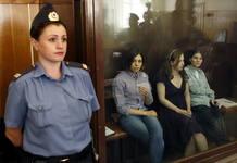 Las tres integrantes del grupo Pussy Riot acusadas de gamberrismo permanecen en una sala acristalada durante la vista del juicio