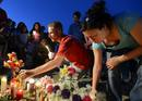 Konye places candles with other mourners during a vigil for victims behind a theater where a gunman open fire in Aurora, Colorado
