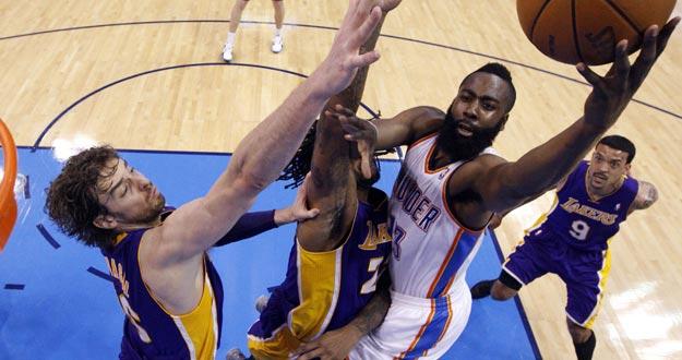 El jugador de Thunder James Harden (d) intentar encestar ante la marca de Pau Gasol (i) y Jordan Hill (c) de Lakers.