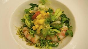 Langostinos de Sanlúcar sobre ensalada de primavera, vinagreta de mango y crujiente de pistachos.