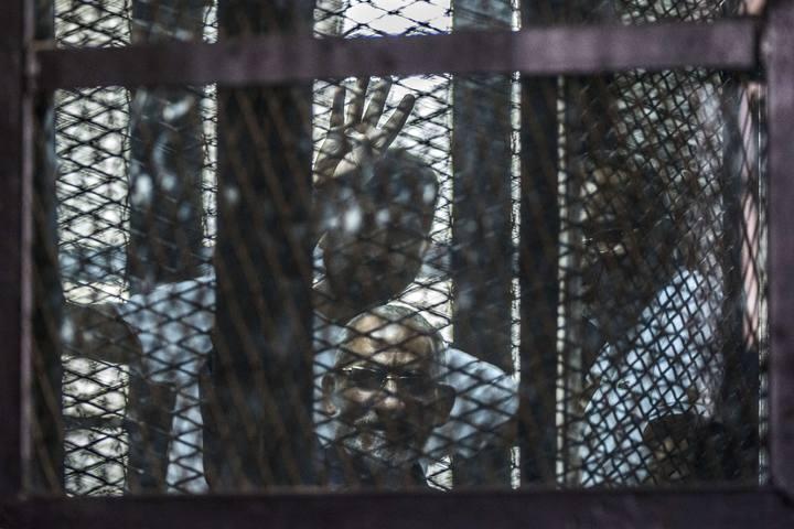 El líder de los Hermanos Musulmanes, Mohamed Badie, hace gestos desde la celda en la que atiende su juicio en la prisión de Tura (Egipto), el pasado 3 de agosto