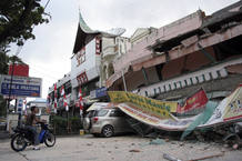 A man sits on a motorcycle outside a collapsed shopping mall after an earthquake hit Padang