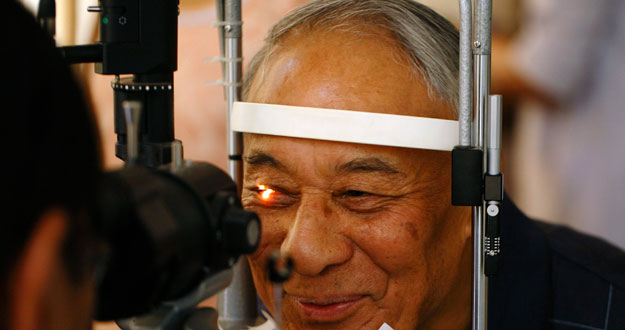 A man smiles as he receives his routine eye check-up after removing his cataracts in Kathmandu