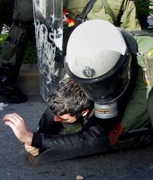 Agentes antidisturbios arrestan a un manifestante frente a la sede central de la policía en Atenas.