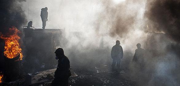 Un manifestante opositor utiliza máscara antigas para protegerse en Kiev