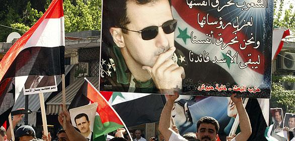 Un manifestante pro-Asad sujeta una pancarta con la imágen del presidente de Siria