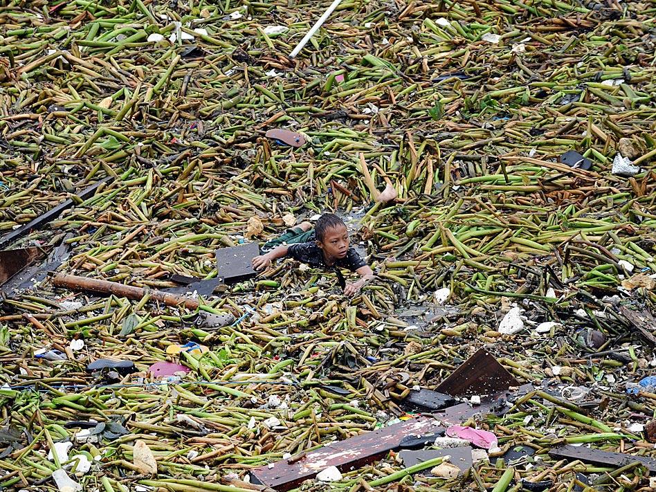 En Manila, capital filipina, la tormeta tropical Saola redujo a la nada la casa de muchos. Al menos una persona murió y un millón de hogares perdieron la luz a causa de este temporal. En la imagen, un niño nada entre los escombros y la basura.