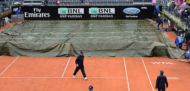 Los operarios del Masters 1000 de Roma tapan la pista con una lona por la lluvia.