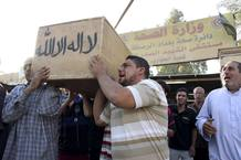 Men carry the coffin of a victim, killed in one of Thursday's bomb attacks, during a funeral in Sadr City, northeastern Baghdad
