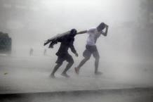 Dos personas luchan contra la fuerza del viento y la lluvia, en la provincia de Isabela (en el norte de Filipinas)