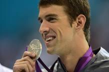 Michael Phelps sonríe con su medalla de oro.