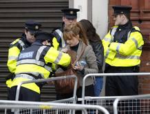 Miembros de la Policía irlandesa registran el bolso de una mujer en Dublín
