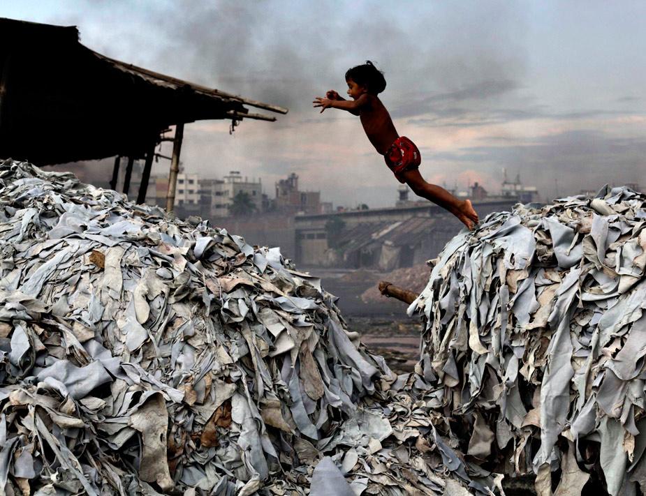Miles de niños intentan cada día dar el salto desde la marginación a una vida digna, donde tengan asegurado el derecho a la alimentación o la vivienda, como este pequeño que vive en un basurero de Bangladesh. REUTERS/Andrew Biraj