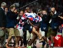 En una noche triunfal para el atletismo británico, Mohamed Farah se ha hecho con el oro en los 10.000 metros ante el jolgorio de los londinenses. En la imagen, lo celebra con su hija.
