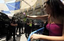 Una manifestante 'indignada' del Movimiento 15M ofrece una flor a los policías que impiden la entrada en Sol, Madrid.