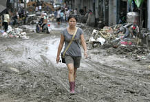 A woman walks in a mud-covered street after Typhoon Morakot swept Taiwan at Chishan township in Kaohsiung county