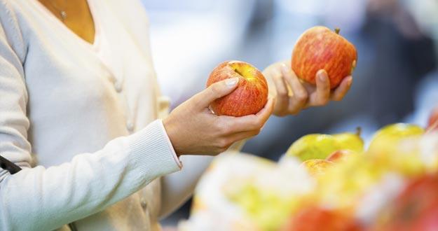 Mujer comprando frutas en un mercado.