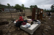 A woman and her son rest on a bed after their home was destroyed by a landslide in Amatitilan