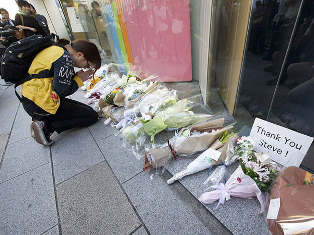 Una mujer reza frente a la tienda Apple de Tokio