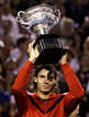 Spain's Nadal holds up the trophy after winning his men's singles final match against Switzerland's Federer at the Australian Open