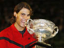 Spain's Nadal bites the trophy as he poses after winning his men's singles final match against Switzerland's Federer at the Australian Open