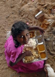 Una niña come en un colegio de la India