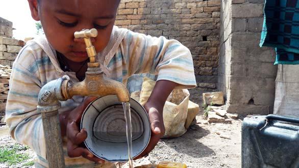 Un niño coge agua en la ciudad de Wukro, Etiopía