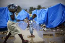 Un niño cruza un charco de agua en medio del fango que dejaron las fuertes lluvias en un campamento improvisado en Cité Soleil en Puerto Príncipe.