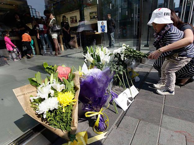 Un niño en Pekín deja flores en homenaje a Jobs
