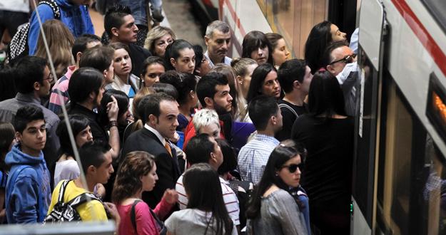 Numerosos pasajeros esperan para entrar en un tren, en la madrileña estación de Atocha