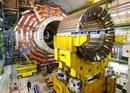 A technician walks under the core magnet of the CMS experiment at the CERN in the village of Cessy