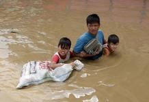 Un padre ayuda a sus hijos a cruzar una calle completamente inundada, en la población de Santa Cruz, en la provincia de Laguna, al sur de Manila (Filipinas),