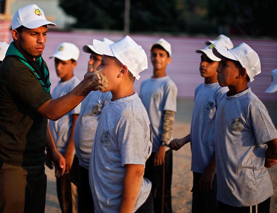 En Palestina, Hamas organiza centenares de campamentos escolares en el estío. Un entrenador pone arena en el interior de la boca de un niño palestino durante el entrenamiento. REUTERS/Suhaib Salem