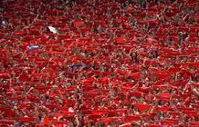 Los asistentes al Chupinazo elevan sus pañuelos rojos al cielo