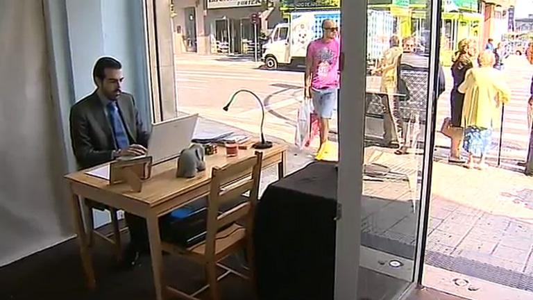 Un joven de 28 años se expone en un escaparate de su barrio para buscar empleo