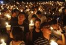 Participants hold candles as they join the celebration of Earth Hour in Manila's Makati financial district