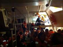 Pasajeros con los salvavidas puestos intentan salir en botes de rescate del crucero 'Costa Concordia'