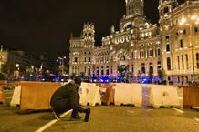 Una persona se parapeta con una botella en la mano frente a los antisturbios en la plaza de la Cibeles a última hora del 14-N