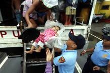 Un policía asistiendo a un bebe durante la evacuación de un barrio marginal de Manila