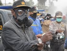 La Policía distribuye máscaras a los habitantes de Malang, en la provincia de Java Oriental, para protegerse de las cenizas volcánicas