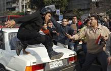 Un policía salta sobre un coche durante la protesta antigubernamental en el centro de El Cairo.