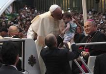 El papa besa a un bebé durante su recorrido por las calles de Río de Janeiro con motivo de la celebración de la JMJ en Brasil