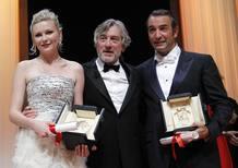 El presidente del jurado de Cannes, Robert de Niro, posa con los actores premiados, Jean Dujardin ('The Artist') y Kirsten Dunst ('Melancholia'), durante la ceremonia de clausura del festival