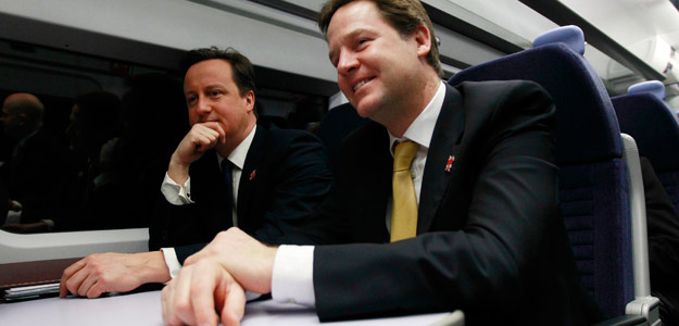 El primer ministro, David Cameron (izquierda), junto al viceprimer ministro Nick Clegg, en el tren que les lleva a la reunión de gabinete, celebrada en la sede de los Juegos Olímpicos 2012