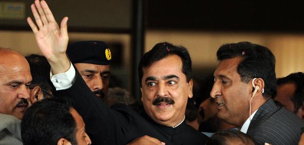El primer ministro de Pakistán, Yusuf Raza Guilani, en el centro, escultado a su llegada al Supremo el 26 de abril