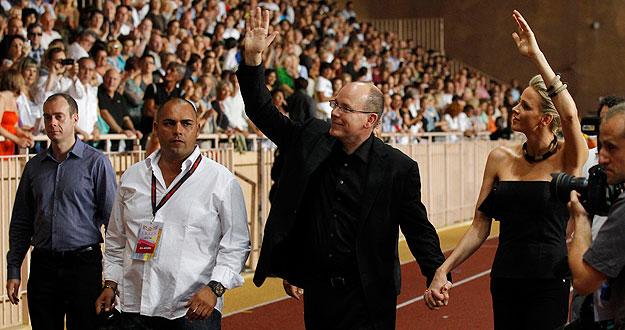 El príncipe Aberto II y su prometida saludan a su llegada al concierto de The Eagles