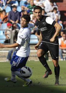 El centrocampista argentino del Real Zaragoza, Lucas Wilchez (i), intenta robar la pelota al defensa del Málaga CF, Jesús Gámez