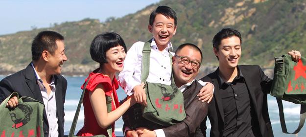 """El realizador Wang Xiao Shuai, en el centro sosteniendo al niño, y los actores de """"11 Flowers""""."""