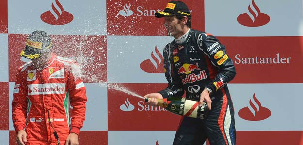 Red Bull Formula One driver Mark Weber of Australia (R) sprays Ferrari Formula One driver Fernando Alonso after winning the British F1 Grand Prix at Silverstone, central England