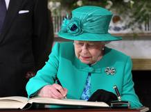 La reina Isabel II firma el libro de visitas de la residencia presidencial de Irlanda